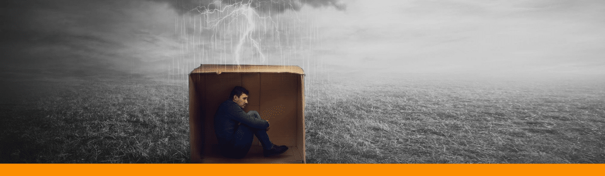 man hiding in box from bad weather